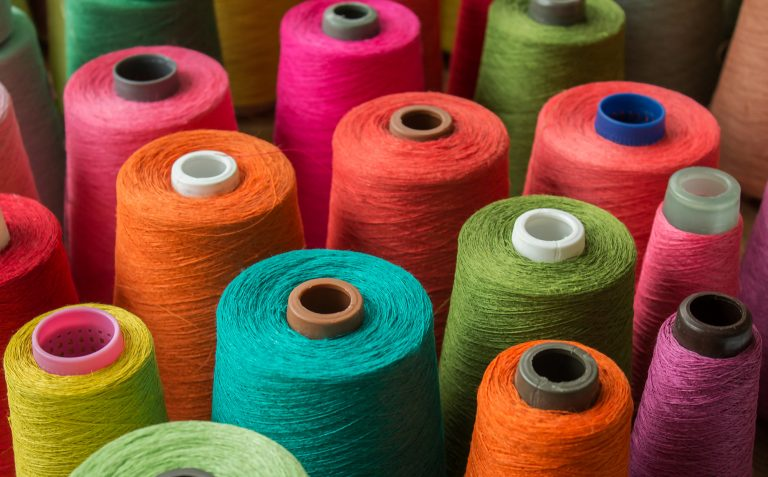 Different coloured cotton reels to make textiles